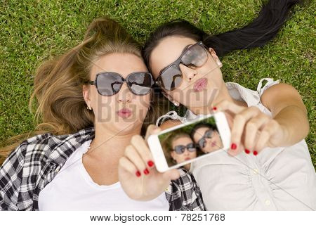 Female best friends lying on the grass and taking selfies