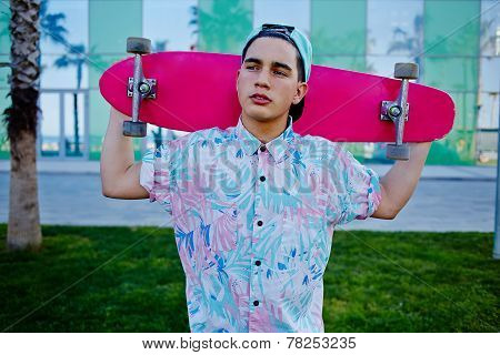 Young stylish man in bright summer clothes standing with pink long-board on beautiful glass backgrou