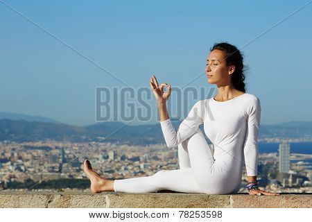 oga on high altitude with big city on background young woman seated in yoga pose on city background