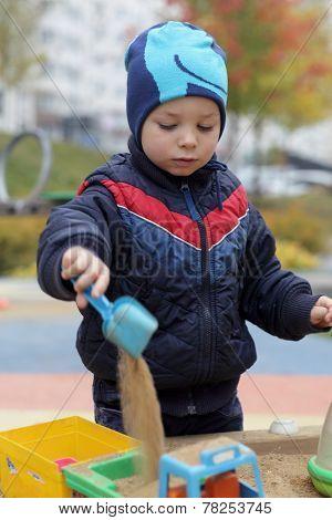 Kid Playing In Sandbox