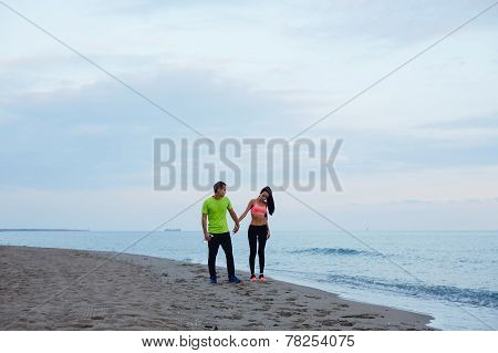 Sport couple walking along the beach resting after workout, couple of runners resting after fitness