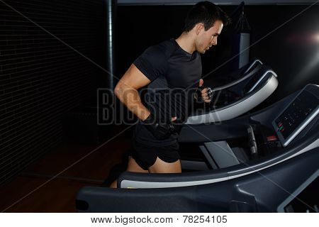 Man running in a gym on a treadmill looking to the screen attractive young man training indoor