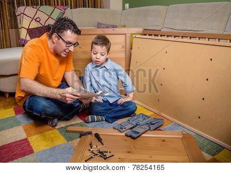 Father and son reading instructions to assemble furniture