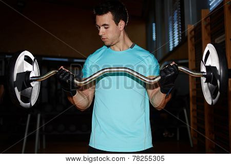 Young man training indoor man doing heavy dumbbell exercise for biceps