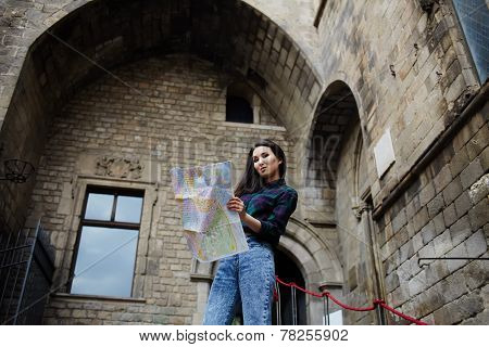 Beautiful tourist woman on vacation with a map in antique gothic city