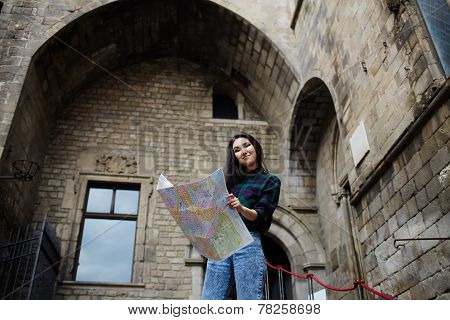 Young tourist girl holding city map in the hands smiling charming girl studying city map