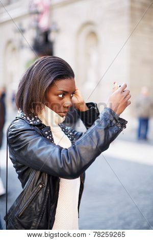 Beautiful woman making up using a smart phone as a mirror chiming young girl looking on a mirror