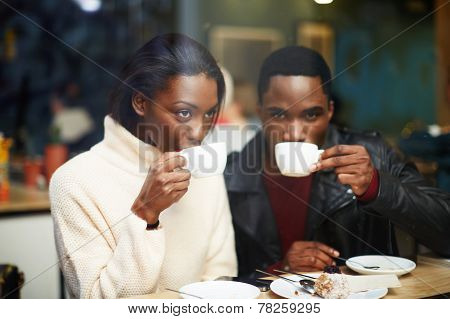 Friends at breakfast having coffee, two young friends holding cups drink coffee in cafe