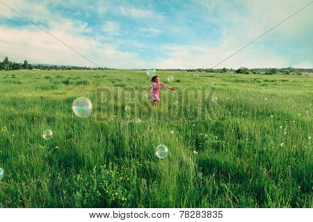 Child Playing Among Soap Bubbles In Summer