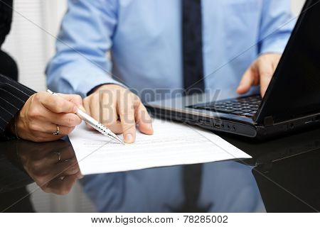 Businesswoman And Businessman  On Meeting In Office  Analyzing Document