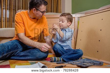 Father and son assembling a new furniture for home