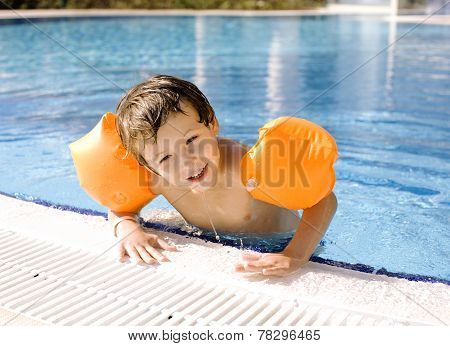 little cute boy in swimming pool wearing handcarves