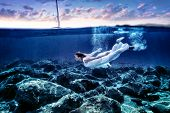 stock photo of wearing dress  - Young woman diving in sunset time - JPG