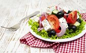 foto of greeks  - Plate with Fresh Greek salad on a wooden background  - JPG