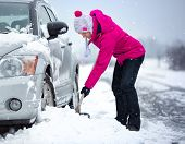 pic of snow shovel  - woman shoveling and removing snow from her car - JPG