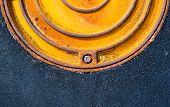 image of manhole  - Rusty metal manhole cover in black asphalt surface - JPG