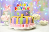 stock photo of cream cake  - Delicious birthday cake on shiny light background - JPG