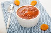 foto of apricot  - Close up of homemade apricot jam with dried apricots on a blue napkin with a spoon - JPG