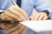 stock photo of writing  - businessman is writing a letter or signing a agreement - JPG