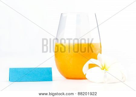 Fresh Orange Juice Glass With White Flower And Blank Tent Note On White Background.