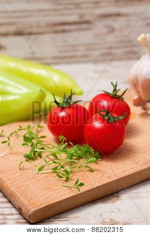 Three Tomatoes And Cress On Wooden Board