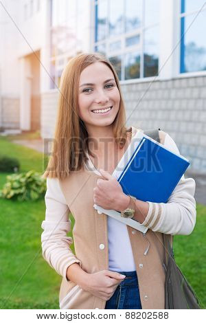 Student Standing With Book And Smiling At Camera