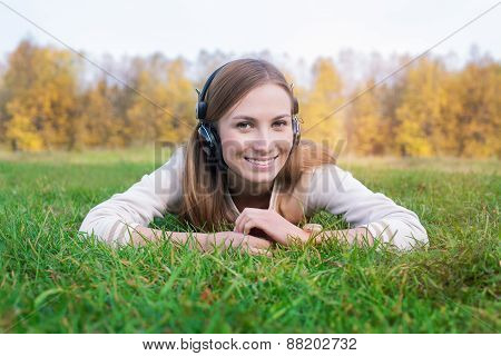 Student Listening To Headphones And Lying On Green Grass