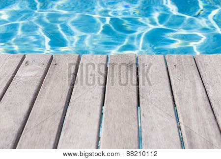 Empty wooden deck by the swimming pool