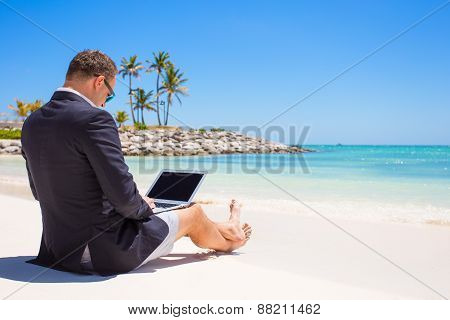 Businessman using laptop computer on tropical beach