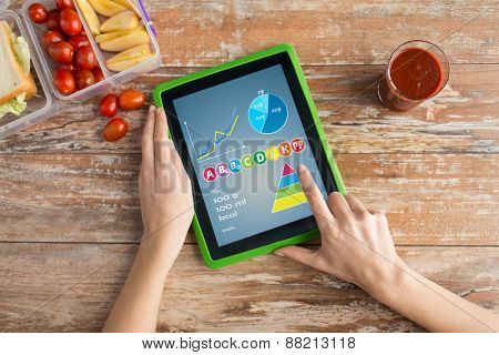 healthy eating, vitamins, dieting, technology and people concept - close up of woman hands with tablet pc computer and food in plastic container on table counting calories at home