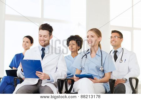 hospital, profession, people and medicine concept - group of happy doctors on seminar in lecture hall at hospital