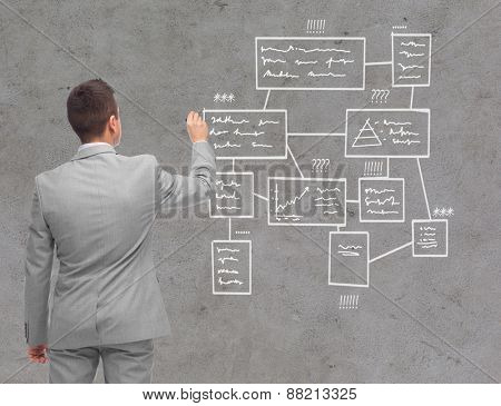 business, people, advertisement , information and office concept - businessman writing or drawing scheme over concrete wall background from back