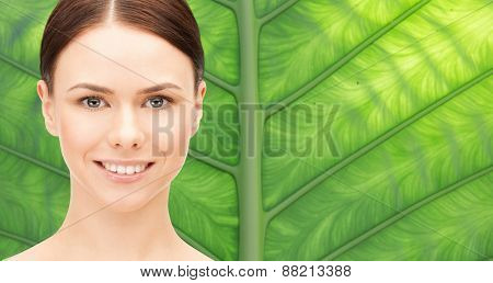 health, people, eco and beauty concept - beautiful young woman face over green palm leaf background