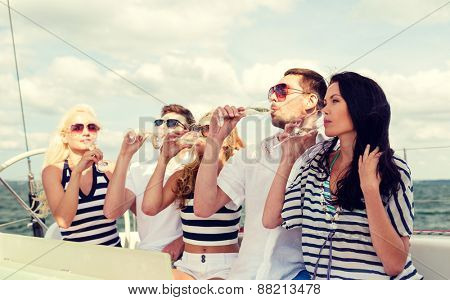 vacation, travel, sea, friendship and people concept - smiling friends with glasses of champagne on yacht