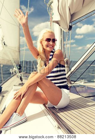 vacation, holidays, travel, sea and people concept - smiling young woman sitting on yacht deck and greeting