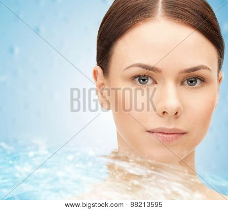 beauty, people, freshness, purity and health concept - face of beautiful young woman and water splash over blue background