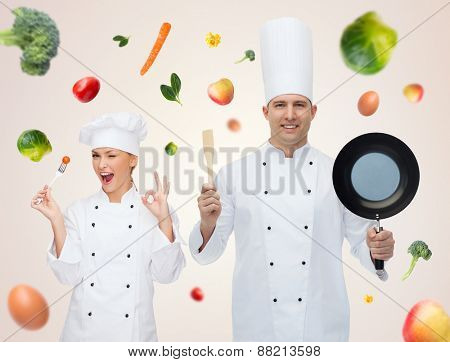 cooking, profession, vegetarian diet and people concept - happy male chef cook holding frying pan and spatula over beige background with falling vegetables