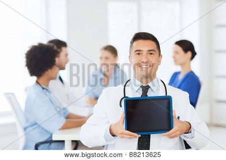 clinic, profession, people and medicine concept - happy male doctor showing tablet pc computer blank screen over group of medics meeting at hospital