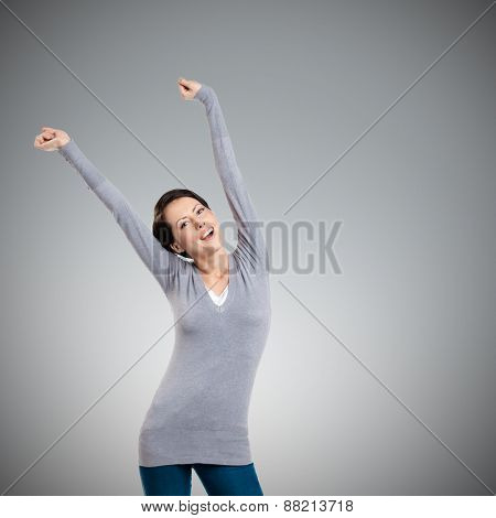 Pretty young girl puts her hands up, isolated on grey