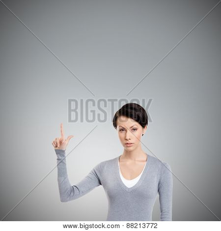 Young woman shows forefinger, attention sign, isolated on grey