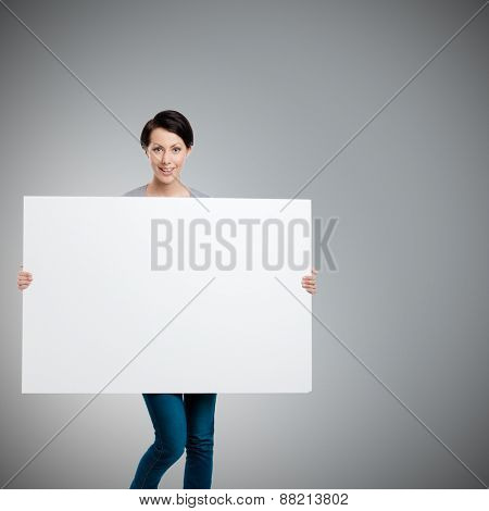 Girl carries a huge sheet of white cardboard , isolated on grey
