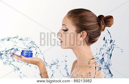Beautiful young woman with moisturizing cream and water splash isolated on white