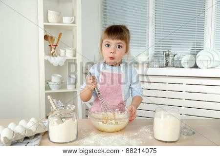 Little girl preparing cookies in kitchen at home