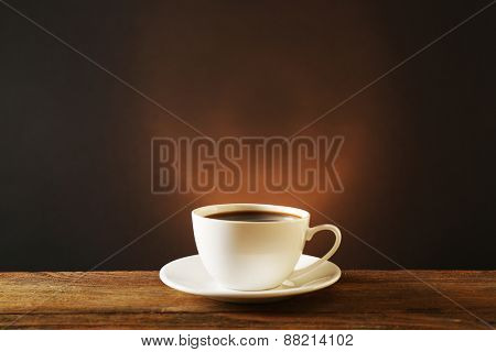 Cup of coffee on wooden table on dark background