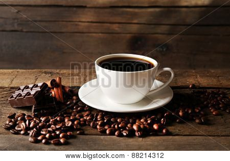 Cup of coffee with grains and chocolate on wooden background