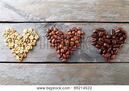Coffee beans in shape of hearts on wooden background