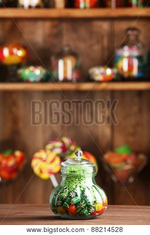 Colorful candies in jar on table in shop