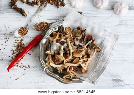 Dried mushrooms in plate with spices on wooden table, top view