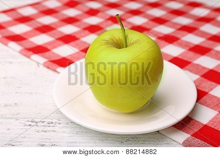 Apple on saucer with napkin on wooden table, closeup