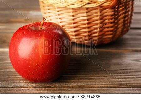 Apple with wicker basket on wooden background